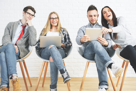 Foto de Group of attractive caucasian guys and girls sitting on modern chairs and using laptops. Technology, teamwork and communication - Imagen libre de derechos
