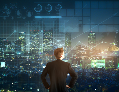 Foto de Back view of young businessman looking into the distance on night city and forex chart background. Trading concept - Imagen libre de derechos