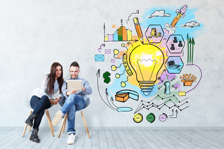 Foto de Attractive young european man and woman sitting on chairs and using tablet on concrete background with business sketch. Technology concept - Imagen libre de derechos