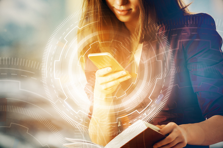 Foto de Attractive young woman using smartphone and holding open book on blurry background with digital business buttons. Innovation concept. Double exposure - Imagen libre de derechos