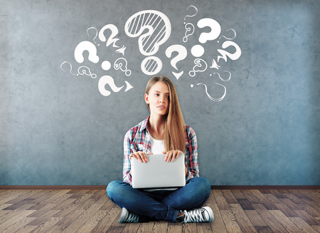 Foto de Attractive young woman sitting on wooden floor with laptop and drawn question marks above on concrete wall. Confusion concept - Imagen libre de derechos