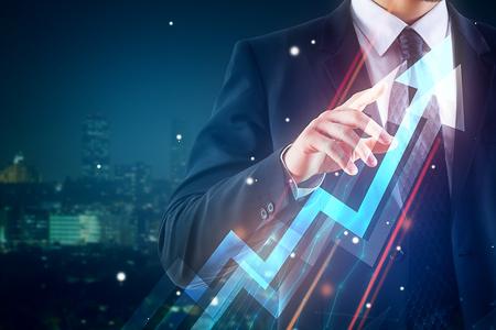 Foto de Businessman pointing at abstract upward chart arrow on night city background. Finance concept. Double exposure - Imagen libre de derechos