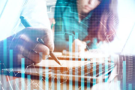 Foto de Close up of businesspeople doing paperwork on office desktop with laptop and abstract business chart. Accounting and analytics concept. Double exposure - Imagen libre de derechos