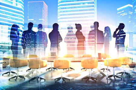 Foto de Abstract silhouettes of businesspeople in conference room with city view. Communication concept. Double exposure - Imagen libre de derechos