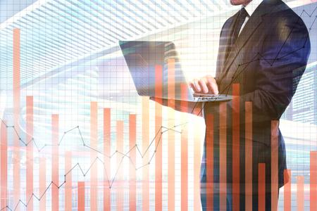Photo pour Unrecognizable businessman using laptop with abstract foirex chart on city background with copy space. Broker concept. Double exposure - image libre de droit