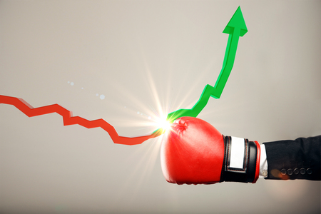 Foto de Boxing glove punching red downward arrow and turning into a green rising one on light background. Economic crisis and success concept - Imagen libre de derechos
