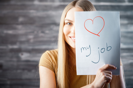 Foto de Attractive young woman with love my job text on wooden background. Success and occupation concept - Imagen libre de derechos