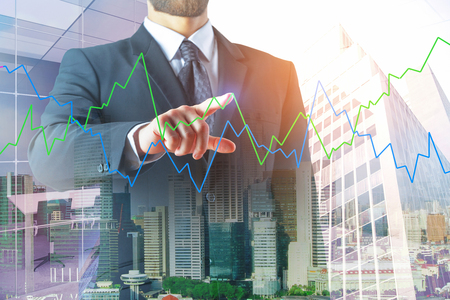 Foto de Investment and monitoring concept. Thoughtful european businessman with abstract forex chart on bright city background. Double exposure  - Imagen libre de derechos