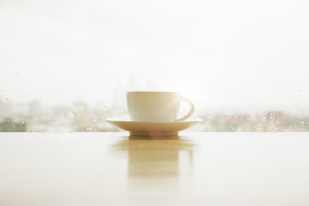 Photo for Coffee cup placed on white windowsill with reflection. Window with rainy blurry morning city view in the backgrouns. Autum or fall mood concept. Mock up  - Royalty Free Image