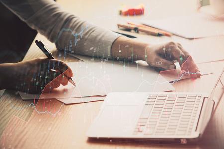 Foto de Close up of hands writing with double exposure of business charts. Financial concept. - Imagen libre de derechos