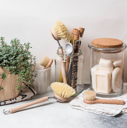Photo pour Zero waste concept. Eco-friendly kitchen set. Brushes, soap in jar, spices in glass tubes and plant in wood flowerpot - image libre de droit
