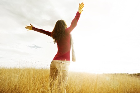 Photo pour Young girl spreading hands with joy and inspiration facing the sun - image libre de droit