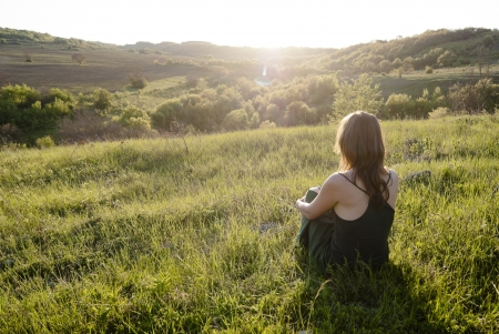 Beautiful young woman sitting on the grass watching sunset surrounded by green nature