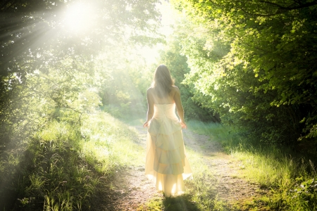 Photo pour Beautiful young woman wearing elegant white dress walking on a forest path with rays of sunlight beaming through the leaves of the trees - image libre de droit