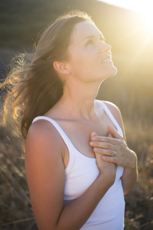 Beautiful young woman with her hands on her chest looking gratefully towards the sky.