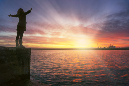 Photo pour Young woman with her arms up in the air with joy and contentment watching the dreamy sunset over the sea. - image libre de droit