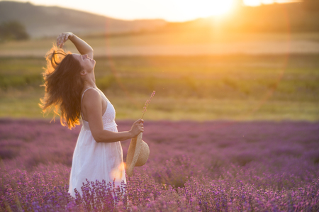 Photo for Beautiful young woman wearing a white dress playing with he long hair in a middle of a lavender field under the golden light of sunset. - Royalty Free Image