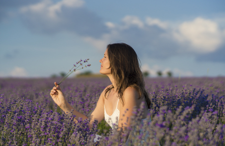Foto de Beautiful young woman holding a bunch of lavender flowers enjoying their fragrance in the middle of a lavender field at sunset. - Imagen libre de derechos