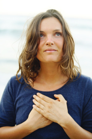 Photo for Beautiful young woman holding her hands on her heart in a silent prayer and gratitude. - Royalty Free Image