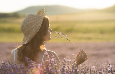 Foto de Beautiful young woman with a straw hat holding a bunch of lavender flowers and enjoying their fragrance in the middle of a lavender field in the light of the setting sun. - Imagen libre de derechos