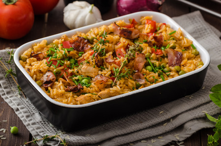 Foto de Cajun chicken with rice,  full of flavor and hot spices with fresh vegetable bio peas - Imagen libre de derechos