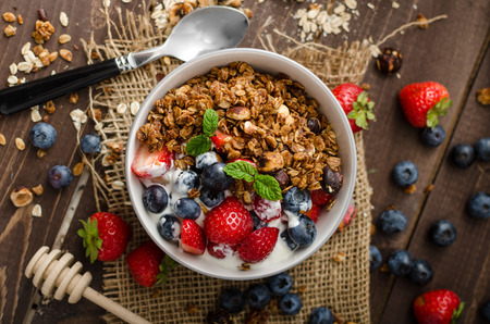Photo for Yogurt with baked granola and berries in small bowl, strawberries, blueberries. Granola baked with nuts and honey for little sweetness. Homemade yogurt - Royalty Free Image