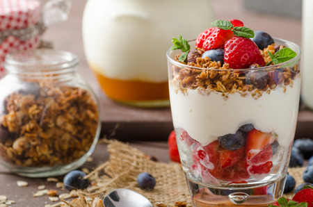 Photo for Yogurt with baked granola and berries in small glass, strawberries, blueberries. Granola baked with nuts and honey for little sweetness. Homemade yogurt - Royalty Free Image