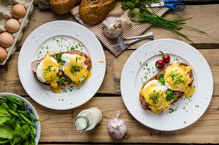 Foto de Eggs Benedict with little salad, milk and fresh herbs - Imagen libre de derechos