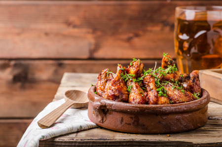 Photo for Grilled chicken wings in homemade Sriracha souce, topped with fresh microgreens, fresh beer behind - Royalty Free Image