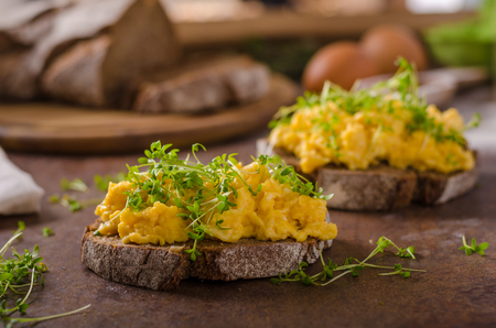 Foto de Scrambled eggs, wholegrain bread with fresh microgreens on top - Imagen libre de derechos