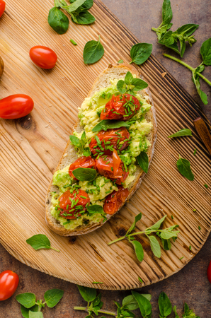 Foto de Avocado spread with tomatoes, roasted tomatoes and herbs on top - Imagen libre de derechos