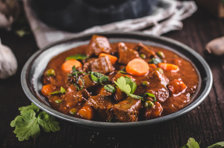 Foto de Beef stew with carrots, food photography, lot of herbs inside stew - Imagen libre de derechos
