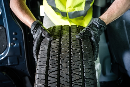 Photo pour Car Tire Replacement. Tire Service. Men with Brand New Tire is Ready For Installation. - image libre de droit