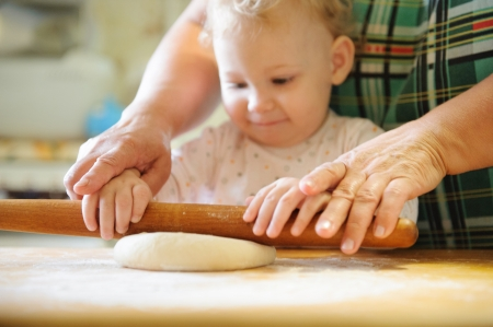 Baby girl rolling dough with her mother