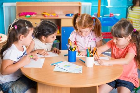 Foto de Group of cute little prescool kids drawing with colorful pencils - Imagen libre de derechos