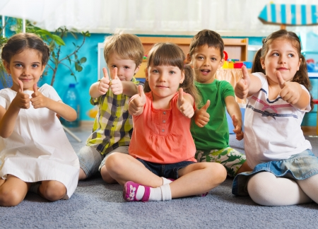 Photo for Five little children sitting on floor with thumbs up sign - Royalty Free Image