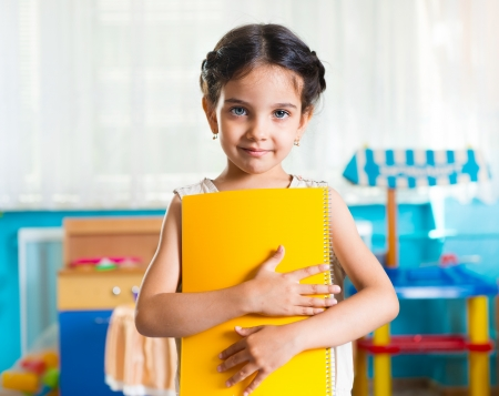 Foto de Beautiful little latin girl portrait with book in daycare - Imagen libre de derechos