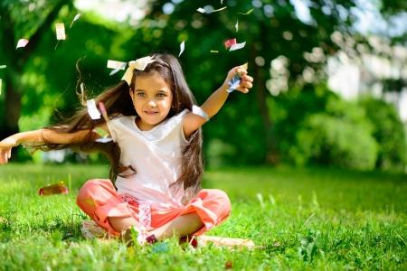 Photo pour Cute hispanic girl throwing confetti at park - image libre de droit