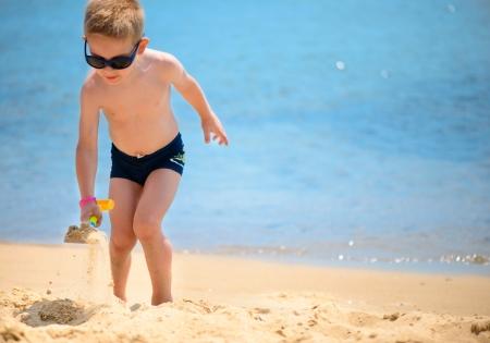 Photo pour Cute little boy playing with sand at ocean beach - image libre de droit