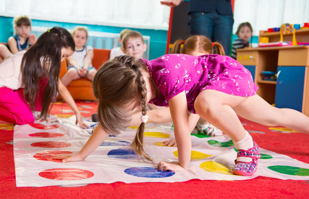 Foto de Cute toddlers playing in twister game at kindergarten - Imagen libre de derechos