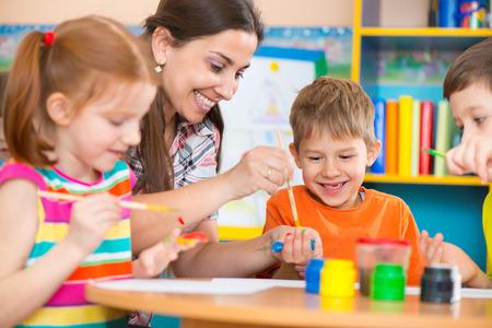 Foto de Cute little children drawing with teacher at preschool class - Imagen libre de derechos