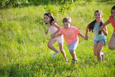 Photo pour Group of happy children playing on meadow - image libre de droit
