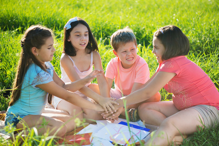 Photo pour Group of happy children playing on green grass - image libre de droit