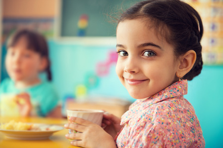Foto de Cute little hispanic girl drinking milk at school - Imagen libre de derechos