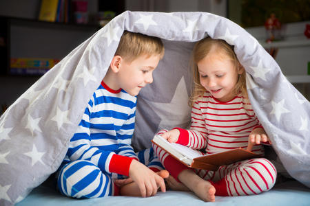 Photo pour Two happy siblings reading book under the cover - image libre de droit
