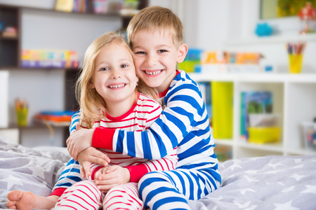 Photo pour Cute little brother and sister in pajamas at home - image libre de droit