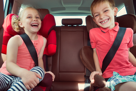 Photo pour Happy kids, adorable girl with her brother sitting together in modern car locked with safety belts enjoying family vacation trip on summer weekend - image libre de droit