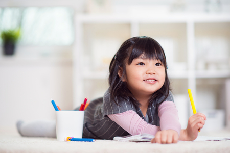 Photo pour Pretty happy little japanese girl lying and drawing with pencils on white capet at home - image libre de droit