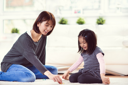 Foto de Pretty happy japanese mother play with her cute little daughter at home - Imagen libre de derechos