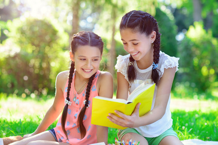Photo pour Happy hispanic girls drawing and studying in summer park - image libre de droit
